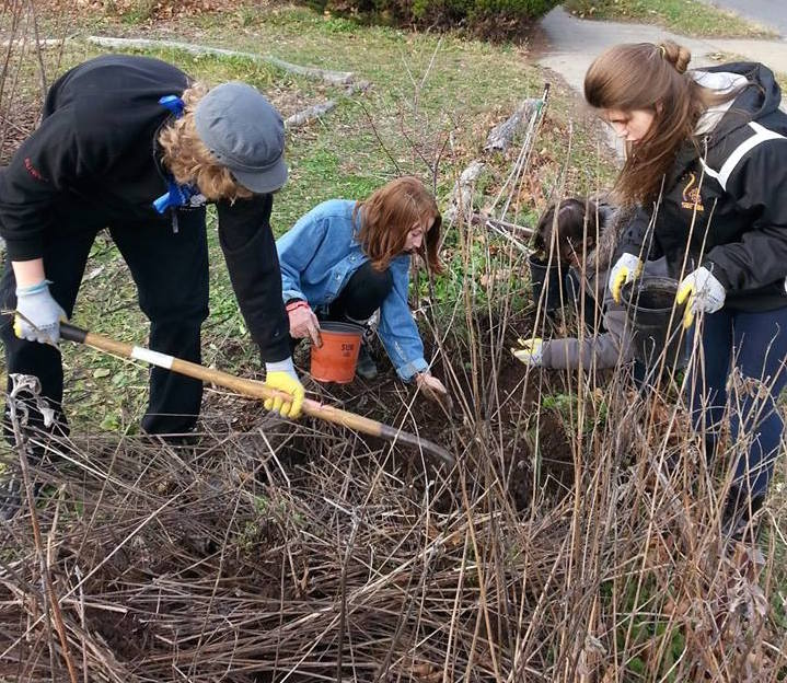 Four Teens from First UU working in a garden with gardening tools cleaning up the garden
