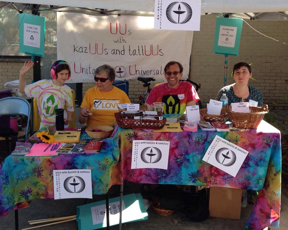 Members of First UU sitting at our information table at the Westcott Festival in Syracuse in 2015
