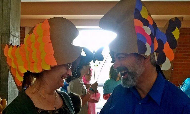 two people wearing funny fish hats smiling at each other