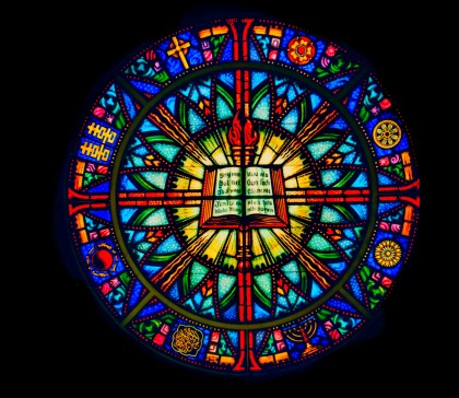 a multi colored image of the chancel window showing a book in the center surounded by 8 symbols representing the different world religions