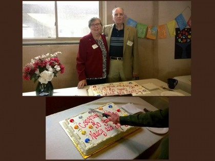 Jerry and Nancy claussen standing at a table with a cake that says 50 years congratulations Jerry and Nancy