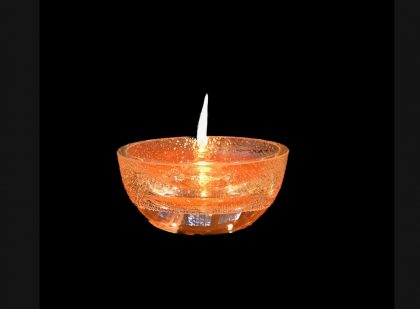 Glass Chalice with lit flame against a black background